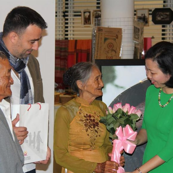 Presenting the world-renowned photograph of a smiling old lady to the Vietnamese Women's Museum